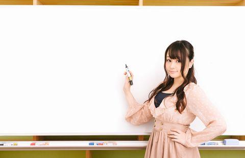 手にペンを持ち、ホワイトボードに書かんとする若い美人女性。