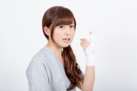 怪我をして包帯を巻いた指を見せつける若い女性。