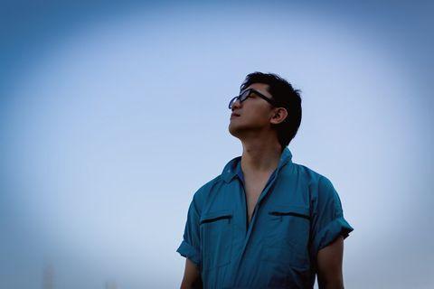 青い作業着を着て空を見上げる男性。