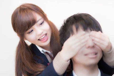 だーれだ?と後ろから目隠しをする若い女性。