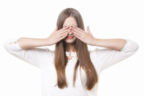 両手で両目を覆い隠す長い金髪の女性。