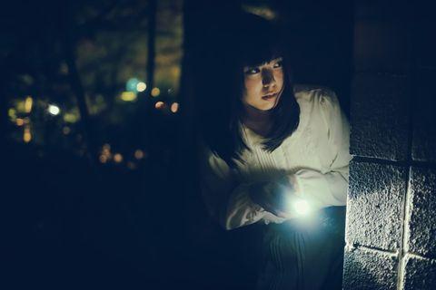 暗闇で懐中電灯を照らす若い白い服を着た女性。