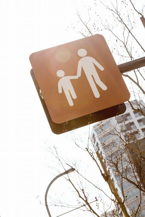 親子が手をつなぐ道路標識。