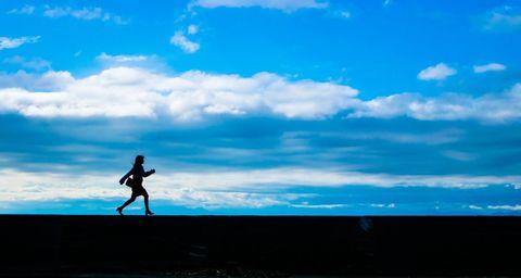 青空を背に歩く女性の影。