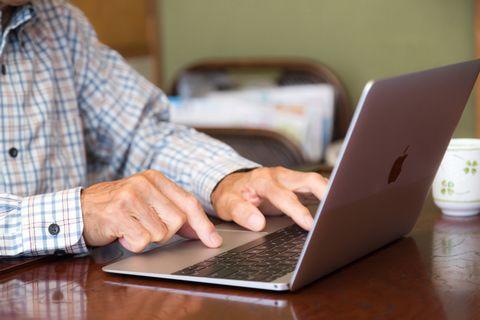 ノートPCで文章を入力する老人の手。