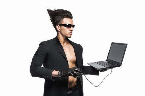 立ったままPCを操作する髪が逆だった黒い服の男。
