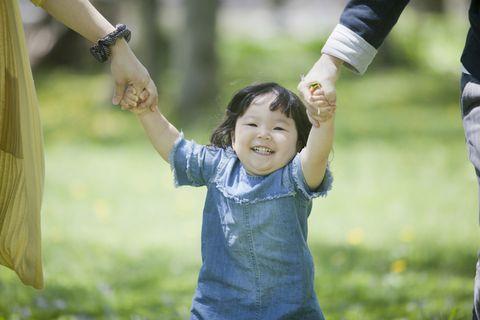 親子3人で手を繋いで歩く幼い子ども。