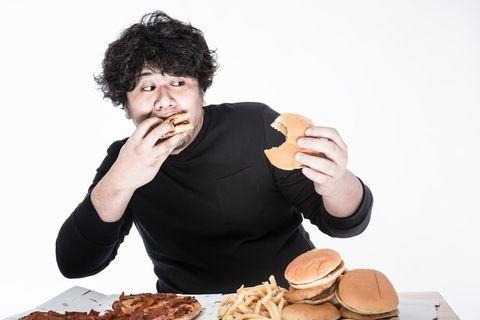 大量の食べ物に食らいつく欲張りな肥満体型の男性。