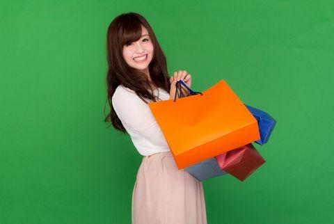両手いっぱいに買物袋を下げる若い女性。