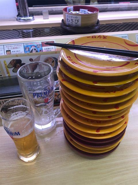 スシローのカウンター席にからのジョッキが2本と皿が15。