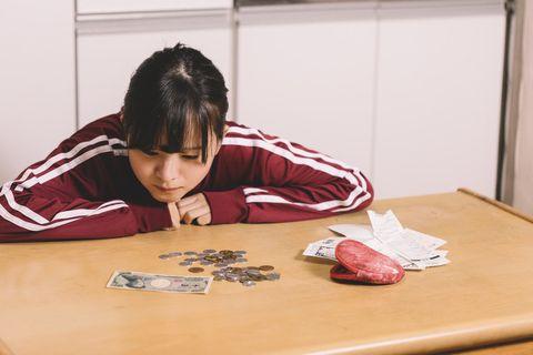 テーブルの上の小銭を数える若いジャージ姿の女性。