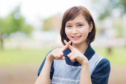 指でバッテンを作るエプロンを来た女性。