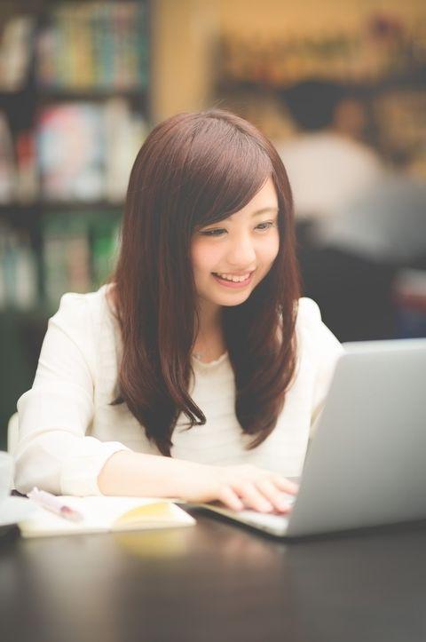 図書館らしきデスクでノートPCのキーボードを叩く髪の長い若く美人な女性。