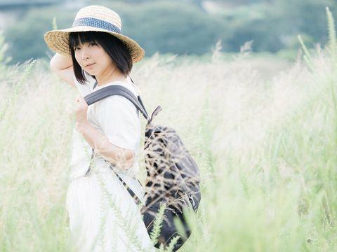 麦わら帽子にリュックを背負った若い女性。