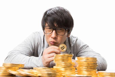 大量のビットコインを疑わしく見る男性。
