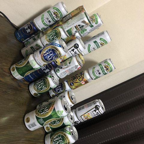 テーブルにつまれた缶ビールの空き缶。