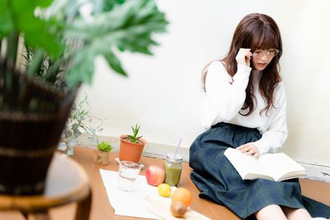 足を伸ばして読書をするメガネをかけた女性。
