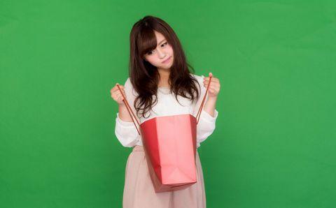買い物袋の中身を見て首をかしげる若い女性。