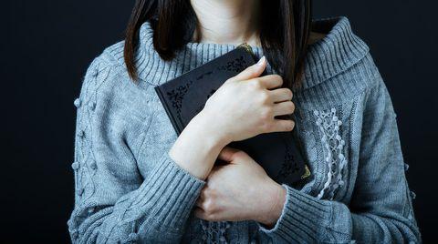 両手で黒いノートを胸の前で抱きしめる女性。