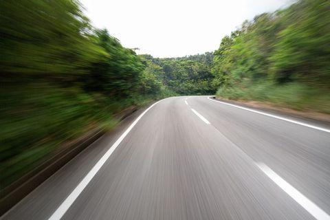 とても速く森の道路を走っているような写真。