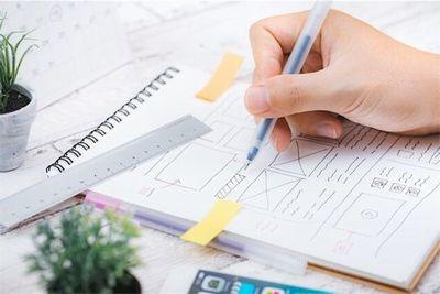 ノートに鉛筆でサイトのデザイン案を組んでいる。
