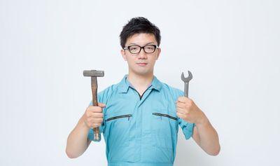 工具を両手に持つ作業着の男性。
