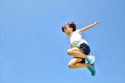 両手いっぱいに広げてジャンプする女の子。