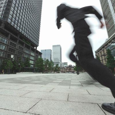 街なかを走るスーツを着た男の後ろ姿。