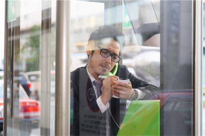 公衆電話ボックスでメモを取る男性。