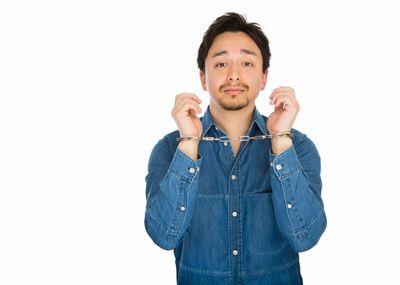 手錠をかけられた男性。