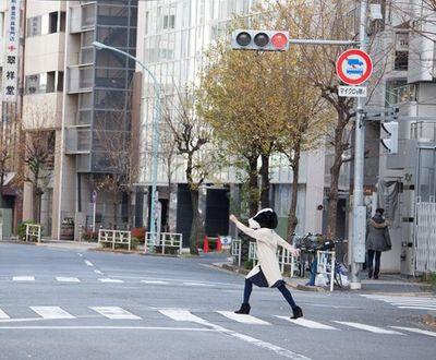 牛のかぶりものをして横断歩道を渡る女性。