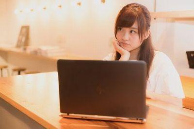 ノートPCを前に悩む若い女性。