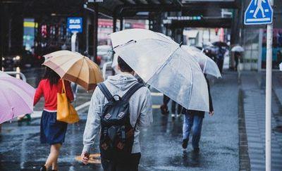 雨の中傘をさして歩く人々。