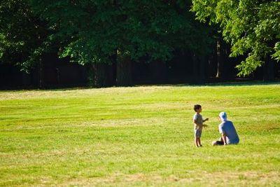草原に座る父と子。
