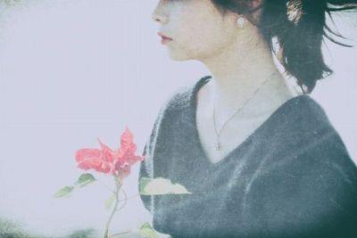 一輪の花を手に持つ哀愁ただよう女性。