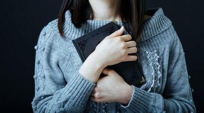 黒いノートを大事そうに胸に抱える女性。