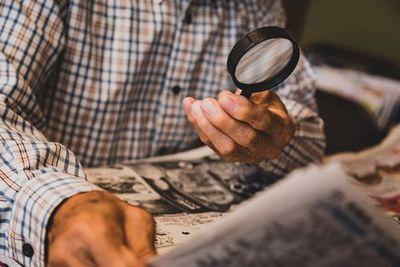 ルーペを使って新聞を読む老人男性。