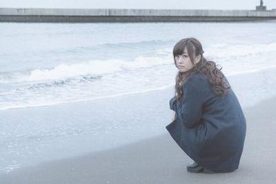 海辺の砂浜で座りこんでコチラを眺める河村友歌。