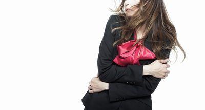 ベジータポーズで心臓を守る黒い服の女性。