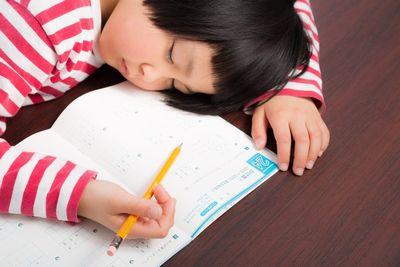 宿題の途中で疲れ果てた小学生。