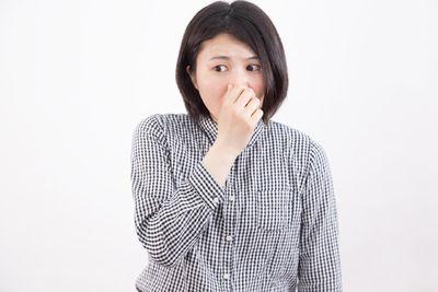 鼻をつまむ女性。