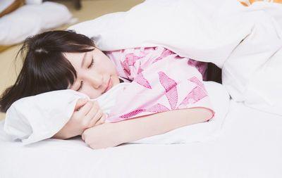 布団で眠る女性。