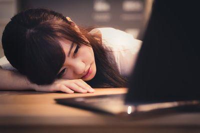 PCを前にうつらうつら寝落ちしそうな女性。