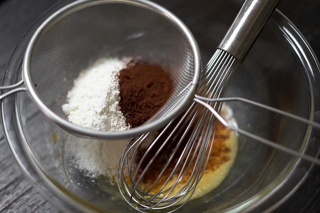 卵液に薄力粉とココアパウダーをふるい入れる様子