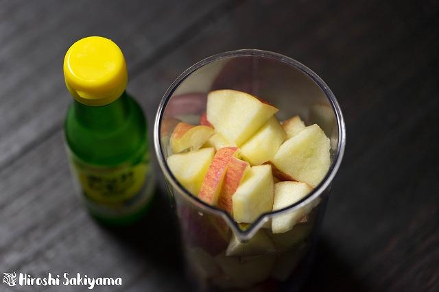 カットした林檎がミキサー容器にはいって、横にレモン汁がある様子