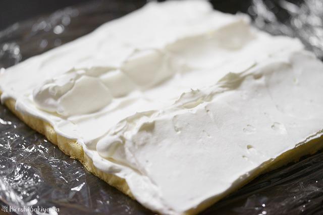 ロールケーキ生地に生クリームを塗った様子(手前1/3と2/3に山が出来るようにクリームを配置している)
