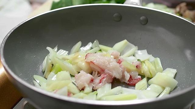 チンゲン菜の芯・蟹を入れて炒める様子