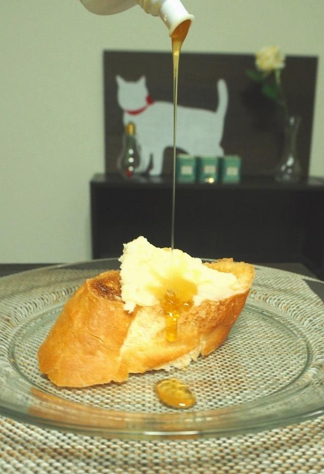 白あんバターを塗ったフランスパンにはちみつを垂らす様子