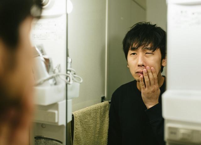 化粧水をつけて肌の状態をチェックする男性