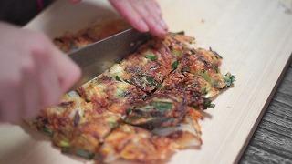 焼き上がったチーズチヂミを正方形にカットする様子